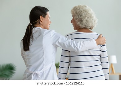 Rear back view of young female doctor physiotherapist caretaker help injured old adult grandma patient assisting holding walking with senior lady at home hospital, elder people physiotherapy concept