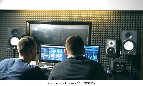 Rear back view of young male sound engineer and music producer discussing and working in the modern recording studio. Audio editor creation a new song on personal computer. Close up Slow motion.