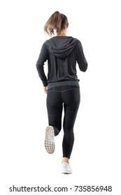 Rear backside view of female runner in hooded sweatshirt running away. Full body length portrait isolated on white background.
