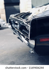 Rear of a beautiful black vintage car parked in a street in Paris, France.