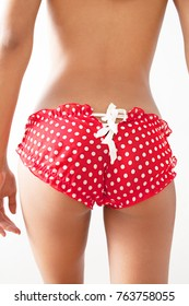 Rear body view of a young woman wearing red polka dot pants with laces against white background, indoors. Perfect bum buttocks, sexy girl with naughty lingerie. Underwear and beauty lifestyle.