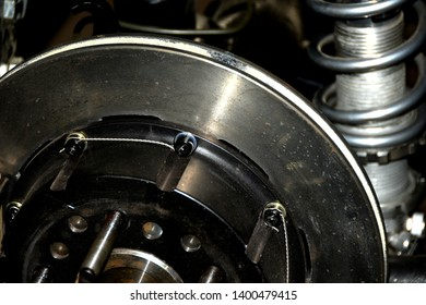 Rear brake disc bolts with anti spinout wires locking the socket cap bolt heads in place for safety.  Automotive background showing blurred foreground and background details.