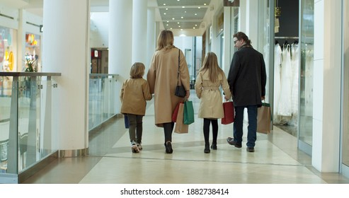 Rear of Caucasian family with kids spending weekend in shopping mall. Smiled parents walking hand in hand with son daughter with bags. Back view on little sister and brother with mother and father.