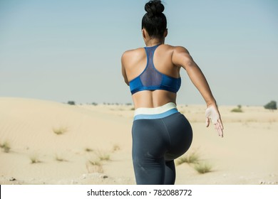Rear closeup view of an athletic Black woman running in the hot dry desert wearing long tight and a sports bra showing her midsection in an extreme sports race