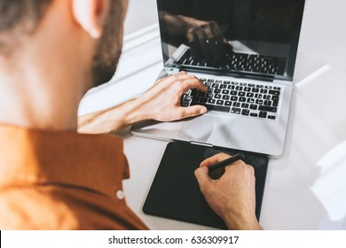 Rear close-up view of young businessman working on generic laptop at desk with pen and tablet, typing, drawing, looking at screen. Male freelancer using notebook, sitting at his workplace on white.