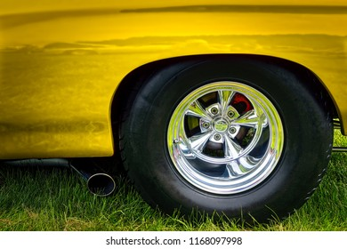 The rear end of an early 1970's American classic car in yellow.
