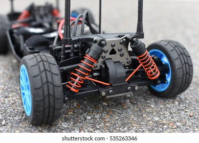 The rear end of a high quality hobby-grade radio controlled model car featuring suspension, differential, rubber tires, blue rims, sway bar, and other parts.