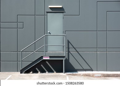 Rear entrance door with metal stairs into industrial building - minimal clean geometric shapes architecture
