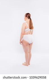 Rear half-turned full-length full-size view photo of obese naked nude woman's body with sagged flabby pigmented skin, dressed in white big-size underlinen, isolated on white background