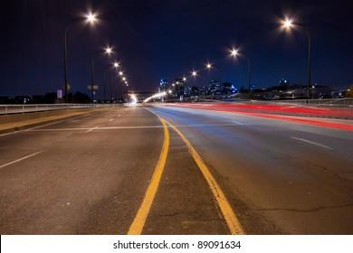 Rear light of cars on a bridge illuminated in Montreal. ( Night Scene )