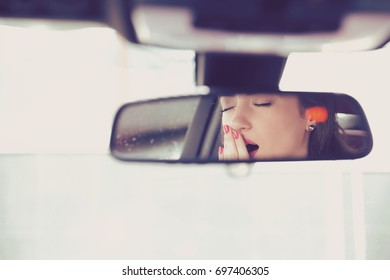 Rear mirror view reflection sleepy yawning woman driving her car after long hour drive.