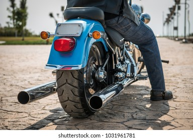 Rear part of a shiny blue metallic motorbike with two exhaust pipes, the rider has blue jeans and black boots. Captured on a shinny day parked on stone road.
