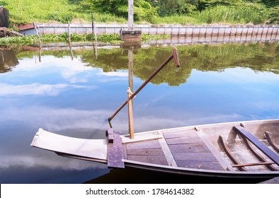 the rear part of Thai ancient rowing boat with long paddle at pier