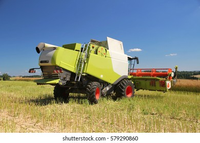 Rear perspective of new combine turning on headland, field of oilseed rape for bio fuel, sunny summer day with blue sky, rape stubble in foreground