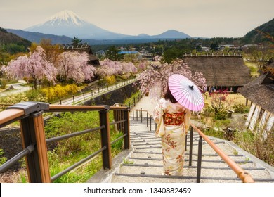 Rear photo of Japanese woman with traditional kimono and umbrella at Saiko Iyashi no Sato Nenba, former farming, village with Cherry blossom or sakura and Mount Fuji or Fujisan, Yamanashi, Japan.