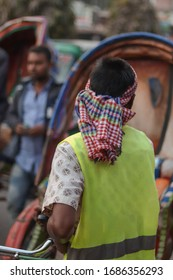 Rear photo of a rickshaw puller in a busy street of Bangladesh.Rickshaw puller with rickshaw is searching for passenger.Due to coronavirus outbreak,its became  very hard for them to living