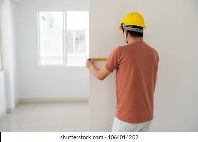 Rear photo of Young Interior engineer man with yellow helmet using measuring tape to measure empty wall of new house. Furtiture or cabinet built in for modern blank home. Real estate industry