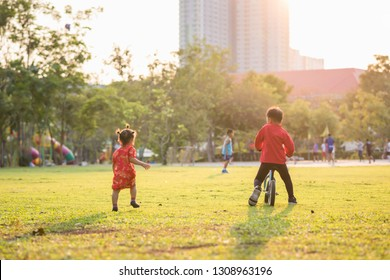 Rear portrait of Chinese brother and little sister with Traditional qipao dress costume ride bike and run in park during sunset. Sport and healthy lifestyle.