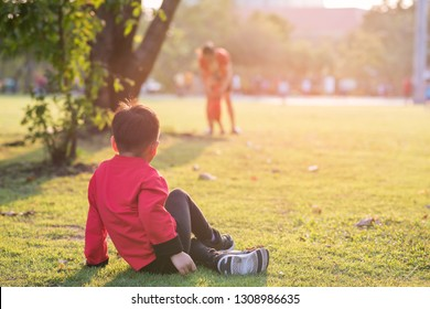 Rear portrait of Chinese brother look at blurred mother and little sister with Traditional qipao dress costume relax in  park during sunset.