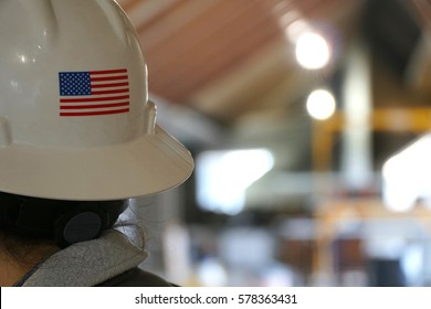 Rear portrait photo behind a female construction worker on a building job site. American flag on back of her white hard hat. Woman foreman in charge of successful development team.