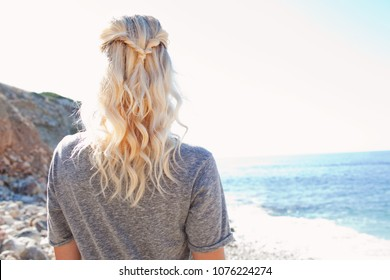 Rear portrait view of nordic tourist woman with healthy blond hair on coastal beach destination, contemplative, sunny holiday, nature outdoors. Healthy wellness living, leisure recreation lifestyle.
