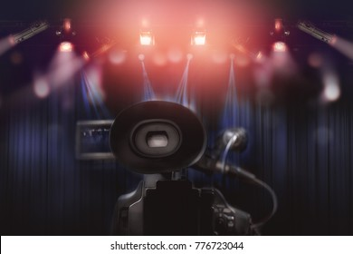 rear of professional video camcorder with set of light hanging in television studio background.