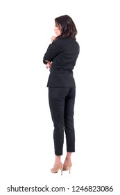 Rear profile view of elegant business woman spectator in suit watching interested at attention. Full body isolated on white background.