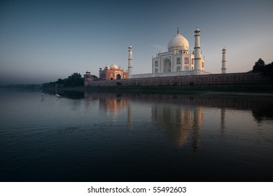 Rear riverside view of Taj Mahal and water birds, yellow billed stork, walk in the calm Jamuna River with early evening sunset reflection in Agra, India. Horizontal copy space