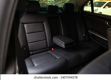 The rear seats of the car in the sedan body are black leather upholstered with the armrest folded down after dry cleaning and washing in a car repair shop. Auto service industry.