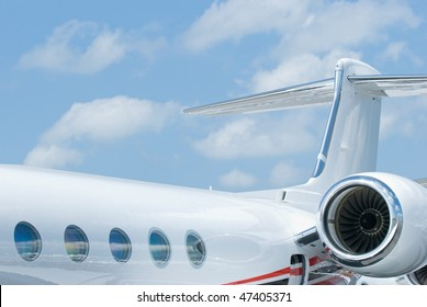 Rear section with tail and engine of white corporate jet with oval windows