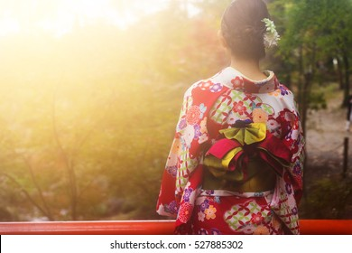 Rear shot of beautiful Japanese girl with traditional red floral pattern kimono dress enjoy autumn foliage colors during sunset with mist at Fushimi Inari temple garden, Kyoto, Japan.