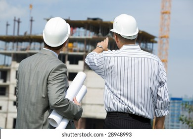 Rear shot of boss pointing at construction with worker near by