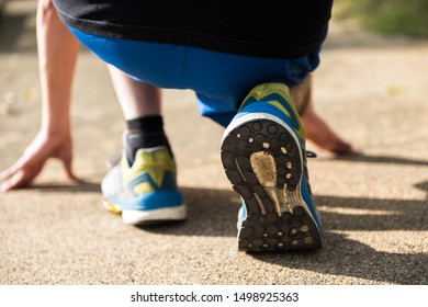 rear shot of closeup feet in running shoes of an athlete to start to run at park with sunset light. Bodybuilding and healthy lifesytle for working man to lose weight.
