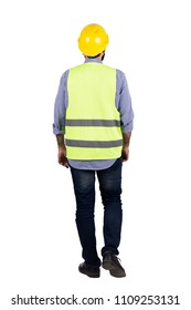 Rear shot of an engineer man wearing his helmet and reflector vest, walking, isolated on a white background