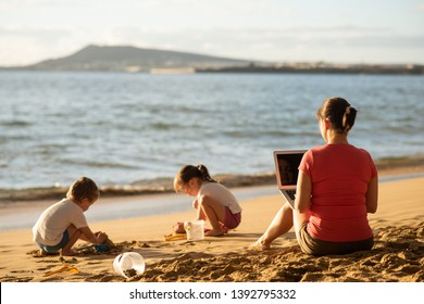 Rear shot of mother working remotely as kids play on the beach