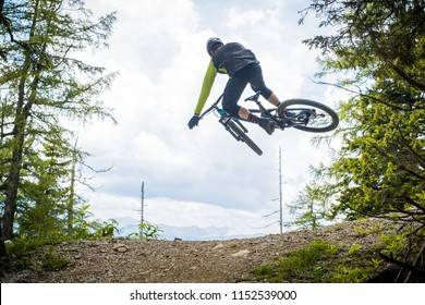 Rear shot of a mountainbiker jumping over a dirt jump in a bike park, surrounded by forest and trees. Green mountain biker in a green environment preforming a tail whip on a double jump.
