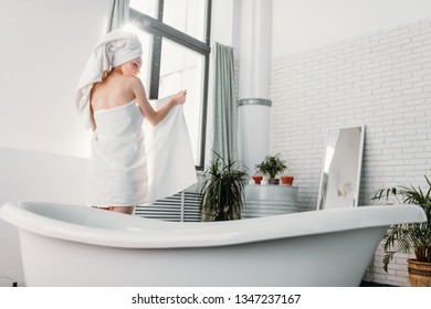 Rear shot of slim young female model wrapped in towel with turban on head, standing between big window and bathtub, using a towel to hide her nudity