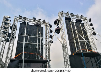 Rear shot of stage lighting and sound Loudspeakers equipment at outdoor stage against blue sky before concert start