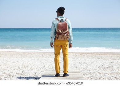 Rear shot of stylish young Afro American backpacker standing on boardwalk on pebble beach, facing vast calm ocean with clear azure water during peaceful morning, admiring amazing marine view