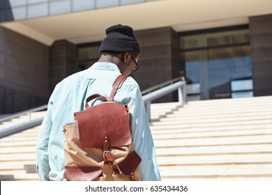 Rear shot of unrecognizable Afro American male student carrying knapsack going upstairs towards modern university building. Black stylish man entering bank. People and urban lifestyle concept