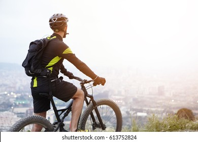 Rear shot of young rider standing on top of hill with booster bike and looking down at foggy city while biking in the morning. Cyclist in black and yellow sports clothes admiring beautiful view