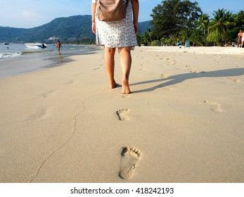 Rear shoulder bag lady and footprints walking on beach
