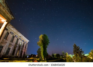 Rear side of the central building of count Potocki palace, in Tulchyn, Vinnytsia region, Ukraine, on a warm spring night against clear dark blue sky full of star tracks