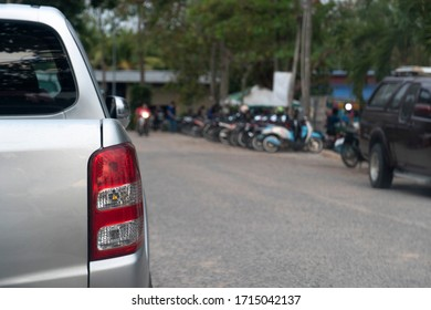 Rear side of pickup car stop on asphalt road beside with blurred of cars parking arear and local market.