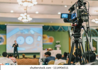 Rear side of Video Cameraman taking photograph to Asian Speaker with casual suit on the stage present the screen in the conference hall or seminar meeting, event and seminar production concept