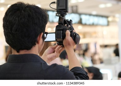 Rear side of Video Cameraman taking photograp to the stage, event and seminar production equipment concept