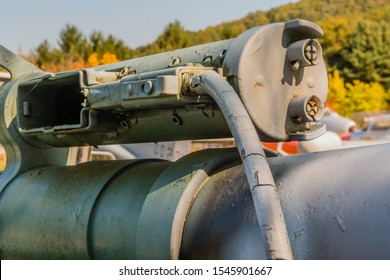 Rear side view of 50 caliber spotting gun with empty magazine holder mounted on top of 106mm recoilless gun on display in public park.