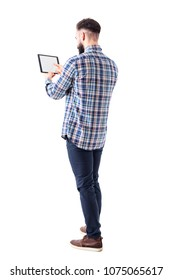 Rear side view of bearded business man pushing button on tablet computer blank touch screen. Full body isolated on white background.
