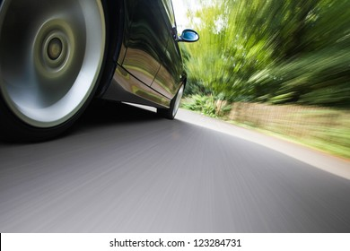 Rear side view of black family car driving fast on forest road