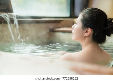 rear side view of charming girl stay in hot spring water and enjoy the view